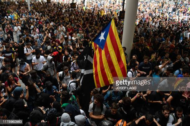 "Protesters holds a Catalan pro-independence ""Estelada"" flag outside El Prat airport in Barcelona on October 14, 2019 as thousands of angry protesters..."