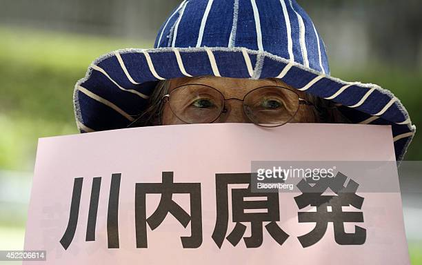 A protesters holds a placard during a demonstration against the restart of Kyushu Electric Power Co's Sendai nuclear power plant in Tokyo Japan on...