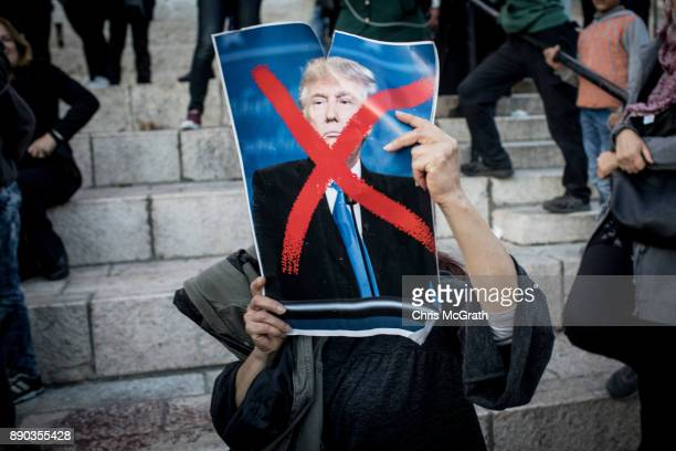 A protesters holds a poster of US President Donald Trump in front of the Damascus Gate at the entrance to the Old City on December 11 2017 in...