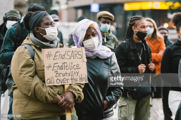"""Protesters holds placard """" End SARS, end police bruality"""" is seen during the protest over Nigerian police brutality in Cologne, Germany, on..."""