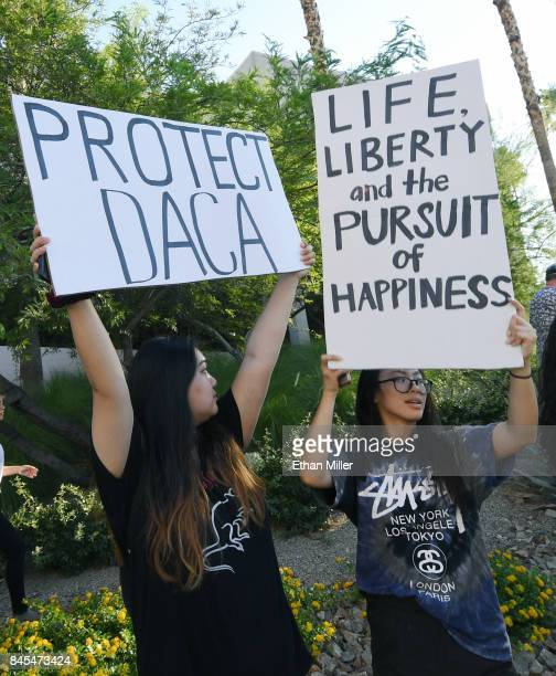 Protesters holds signs across the street from the Trump International Hotel Tower Las Vegas as immigrants and supporters gather for a 'We Rise for...