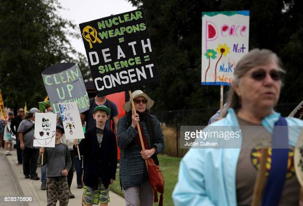 Protesters holds signs during a demonstration against nuclear weapons outside of the Lawrence Livermore National Laboratory on August 9 2017 in...