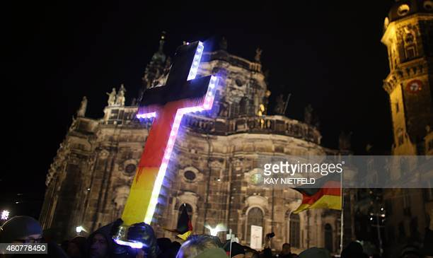 """Protesters holds up an illuminated cross during a rally of the """"Patriotic Europeans Against the Islamisation of the Occident"""" in Dresden, eastern..."""