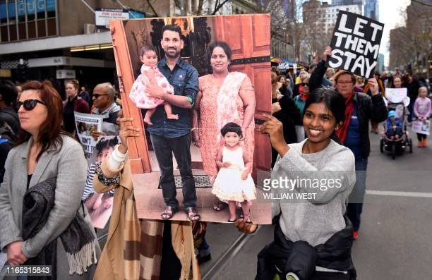 Protesters holds up placards in Melbourne on September 1 during a rally in support of a Tamil refugee family of four -- including two Australian-born...