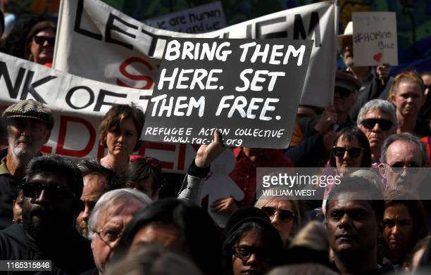 Protesters holds up placards in Melbourne on September 1 during a rally in support of a Tamil refugee family of four including two Australianborn...