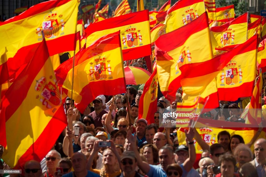 Protesters hols Spanish flags during a demonstration called by 'Societat Civil Catalana' (Catalan Civil Society) to support the unity of Spain on October 8, 2017 in Barcelona. Ten of thousands of flag-waving demonstrators packed central Barcelona to rally against plans by separatist leaders to declare Catalonia independent following a banned secession referendum. Catalans calling themselves a 'silent majority' opposed to leaving Spain broke their silence after a week of mounting anxiety over the country's worst political crisis in a generation. GUERRERO