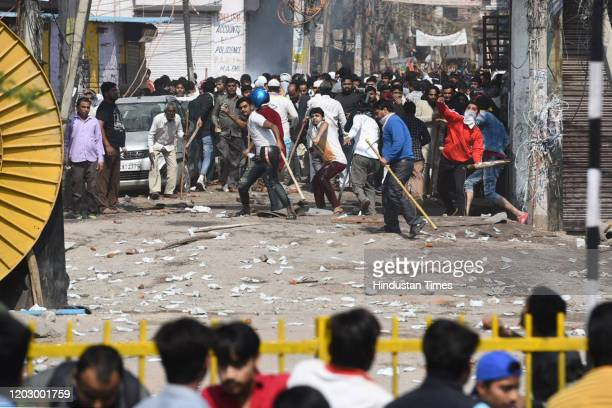 Protesters hurl stones during a clash between anti CAA and pro CAA demonstrations, at Bhajanpura on February 24, 2020 in New Delhi, India. A Delhi...