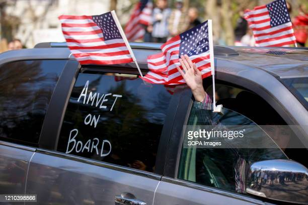 Protesters in a car wave flags during the protest. Protesters gather outside Indiana Governor Eric Holcomb's mansion in the 4700 block of N. Meridian...