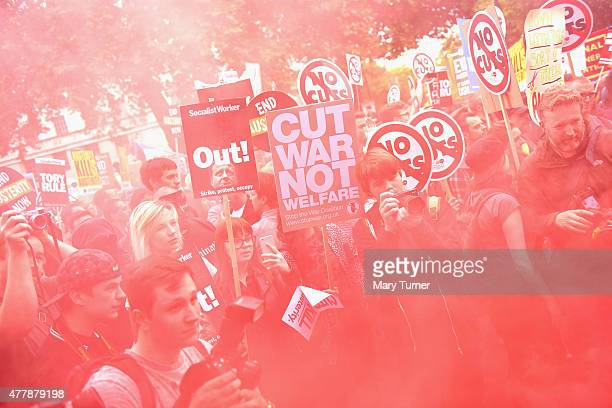 Protesters in central London walk through the haze of a red flare as they demonstrate against austerity and spending cuts on June 20 2015 in London...