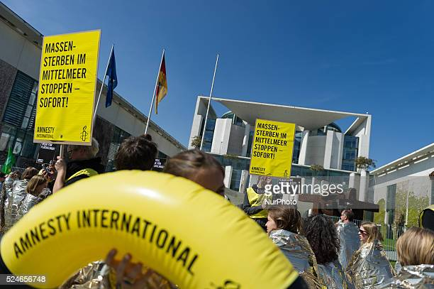 Protesters in emergency blankets are available during a campaign by Amnesty International against the current refugee policy on in Berlin Germany in...