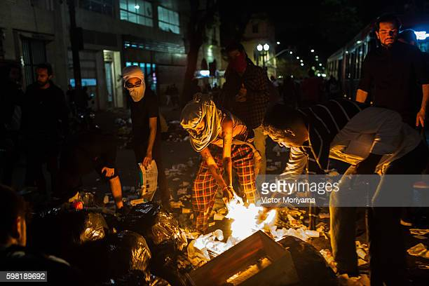 Protesters in favor of former Brazil President Dilma Rousseff burn items in the street during a protest march on August 31, 2016 in Sao Paulo,...