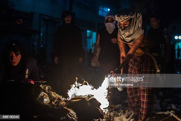Protesters in favor of former President Dilma Rousseff burn items in the street during a protest march on August 31, 2016 in Sao Paulo, Brazil....