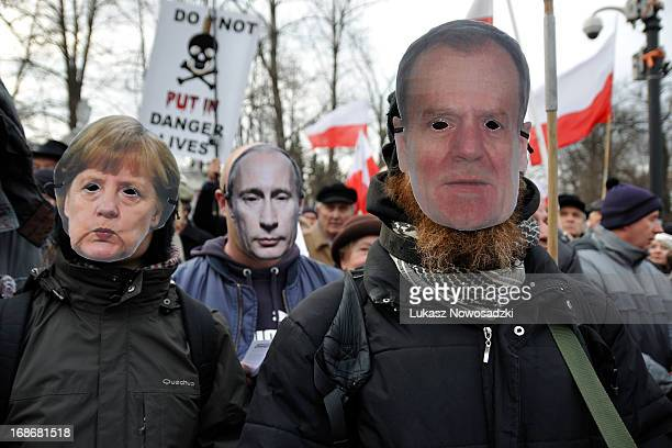 Protesters in masks of Vladimir Putin, Angela Merkel and Donald Tusk during protest near Russian Embassy in Warsaw on third anniversary of crash