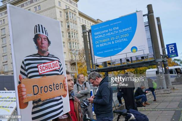 """Protesters, including a man holding a poster of German virologist Christian Drosten with the word """"guilty"""", gather outside the Kosmos events venue..."""