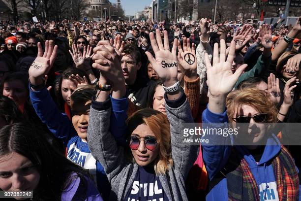 Protesters including Daisy Hernandez of Virginia and Hunter Nguyen of Maryland hold their hands up as they participate in the March for Our Lives...