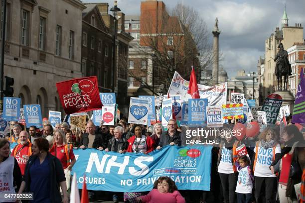 Protesters including Labour Party Shadow Chancellor of the Exchequer John McDonnell and Len McCluskey of Unite march with banners and placards...