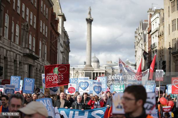 Protesters including Labour Party Shadow Chancellor of the Exchequer John McDonnell and Len McCluskey of Unite march down Whitehall with banners and...