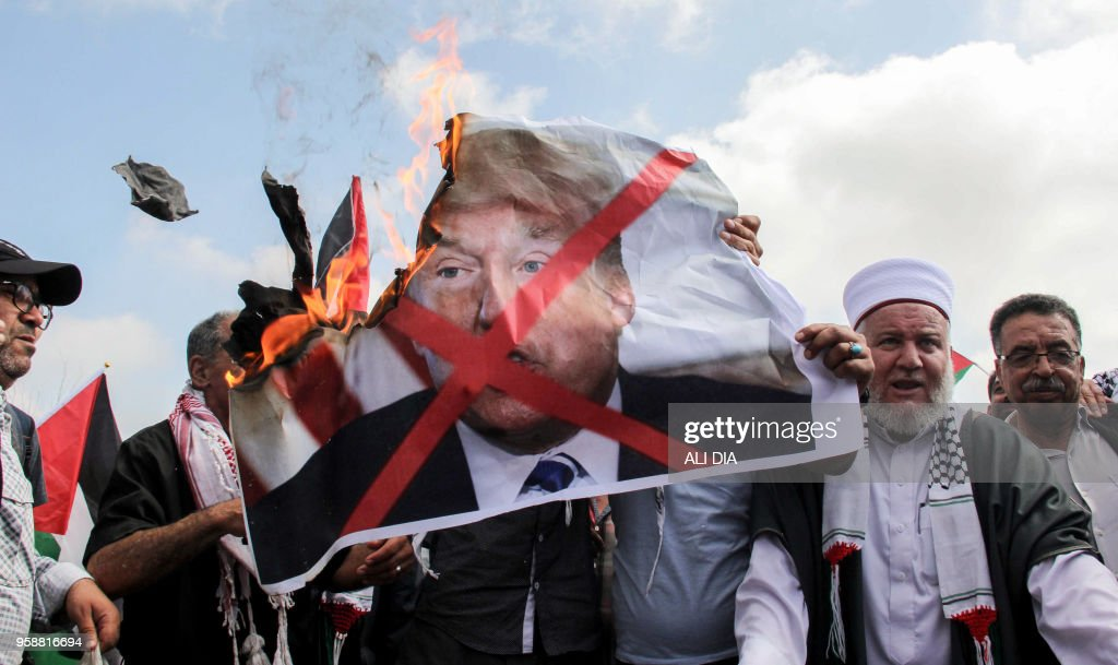 TOPSHOT - Protesters including Lebanese nationals and Palestinian refugees living in Lebanon burn a large print of US President Donald Trump during a demonstration in the medieval Beaufort Castle, known in Arabic as Al-Shaqif Citadel, near the southern Lebanese town of Arnoun in the Nabatiyeh district, on May 15, 2018. - More than 1,000 gathered at the site to protest against the US' decision to relocate its embassy from Tel Aviv to Jerusalem.