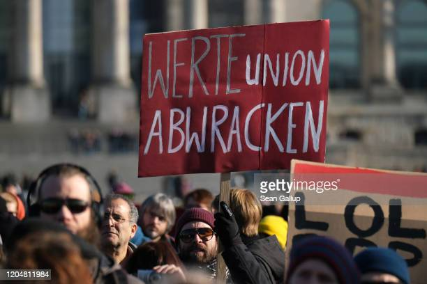 Protesters including one holding a sign demanding the disbandment of the conservative Values Union of the German Christian Democrats demonstrate...
