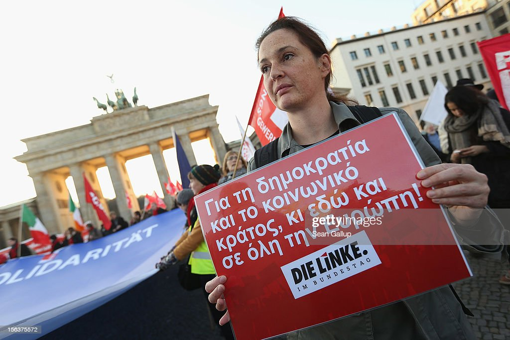 "Protesters, including one that holds a sign in Greek that reads: 'Defend democracy and a socially-oriented state here and in Europe!,' demonstrate in solidarity with the economically-stricken nations of southern Europe during a ""national day of action"" organized by the German Federation of Labour Unions (DGB) on November 14, 2012 in Berlin, Germany. The DGB called for nationwide protests to coincide with strikes taking place today in Spain, Portugal, Greece, Italy and Belgium over government austerity measures meant to combat the ongoing Eurozone financial crisis."