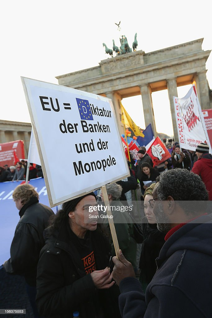 "Protesters, including one that holds a sign that reads: 'EU=Dictatorship of Banks and Monopoly,' demonstrate in solidarity with the economically-stricken nations of southern Europe during a ""national day of action"" organized by the German Federation of Labour Unions (DGB) on November 14, 2012 in Berlin, Germany. The DGB called for nationwide protests to coincide with strikes taking place today in Spain, Portugal, Greece, Italy and Belgium over government austerity measures meant to combat the ongoing Eurozone financial crisis."