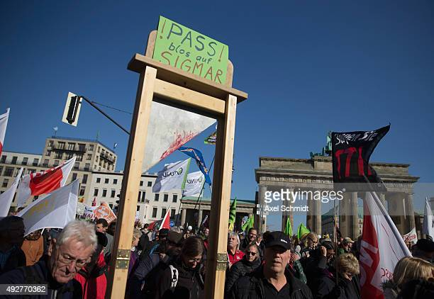 Protesters including some with a fake guillotine with a sign that reads 'Just watch out Sigmar' gather to demonstrate against the TTIP and CETA trade...