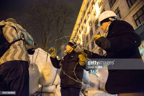 Protesters installing a barbed wire on a new reinforced barricade on Maidan Square on December 11 2013 in Kiev Ukraine Thousands have been protesting...