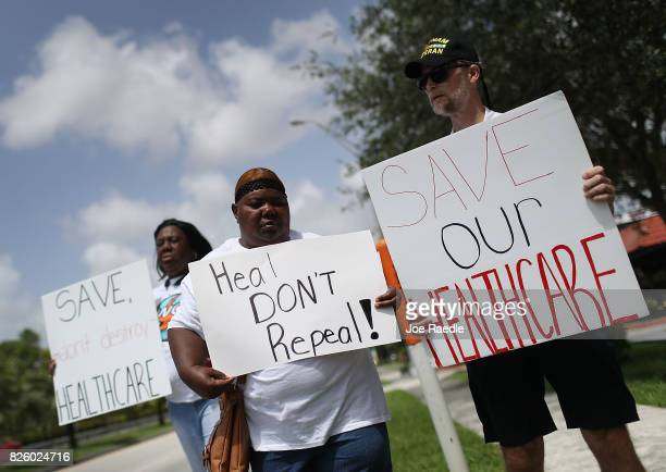 Protesters join together in front of the office of Rep Carlos Curbelo on August 3 2017 in Miami Florida The protesters are asking for Rep Curbelo to...