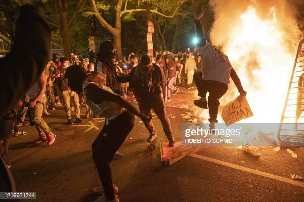 TOPSHOT Protesters jump on a street sign near a burning barricade during a demonstration against the death of George Floyd near the White House on...