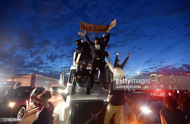 Protesters jump onto a semi truck while blocking traffic on Interstate 580 during a demonstration over the death of George Floyd, a black man who...
