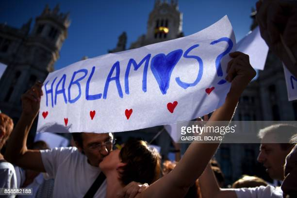 Protesters kiss while holding a placard reading Let's talk during a demonstration called by the Let's talk association for dialogue in Catalonia in...