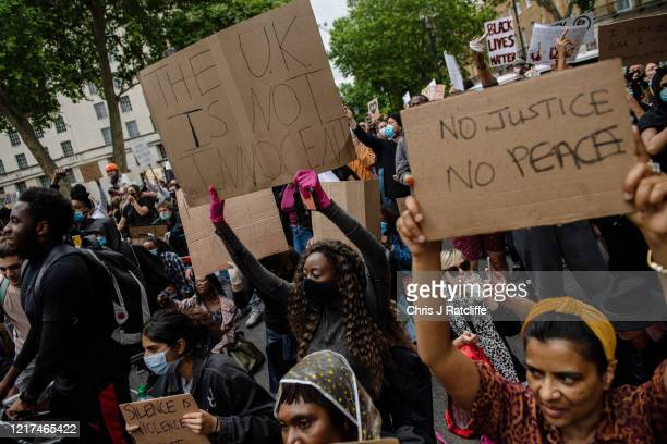 Protesters kneel and hold placards outside Downing Street during a Black Lives Matter demonstration on June 3, 2020 in London, United Kingdom. The...