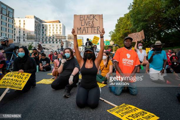 Protesters kneel and hold up signs as they demonstrate the death of George Floyd by closing down and blocking traffic on I-395 in Washington, DC, on...