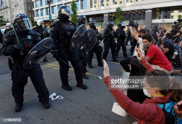 Protesters kneel and hold up their hands in front of a row of police officers in riot gear during a demonstration against the death of George Floyd...