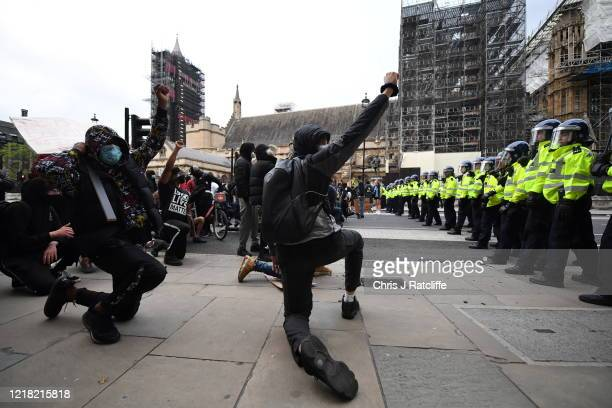Protesters kneel and raise their fists in the air as police officers line up outside the Houses of Parliament during a Black Lives Matter protest in...