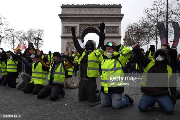 Protesters kneel as they take part in the 'yellow vests' demonstration near the Arc de Triomphe on December 8 2018 in Paris France ''Yellow Vests' is...