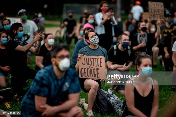Protesters kneel down and hold placards as they take part in a Black Lives Matter vigil on June 3 2020 in the Queens borough of New York City The...