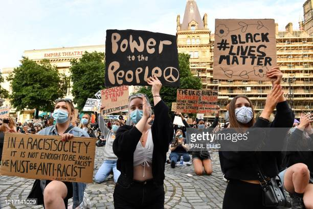 Protesters kneel holding placards outside St George's Hall in Liverpool, northwest England, on June 2 during demonstration after George Floyd, an...