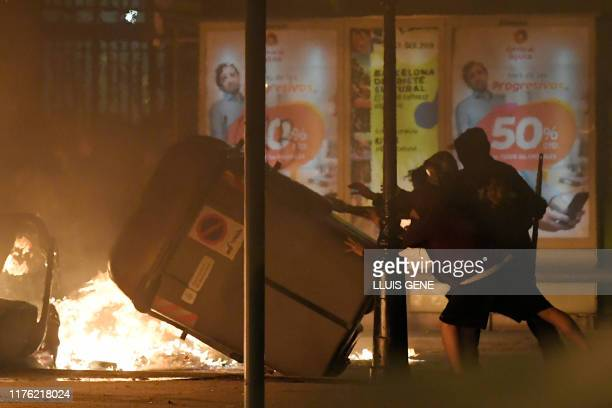 Protesters knock over a skip during a demonstration called by the local Republic Defence Committees in Barcelona on October 16 after police arrested...