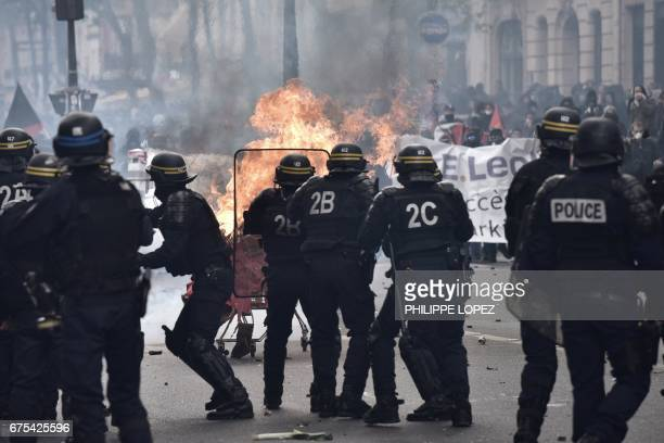 Protesters launch a burning trolley towards French CRS antiriot police officers during a march for the annual May Day workers' rally in Paris on May...