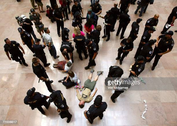 Protesters lay on the floor of the Hart Senate Office Building waiting to be arrested as they are surrounded by Capitol Hill police September 26,...