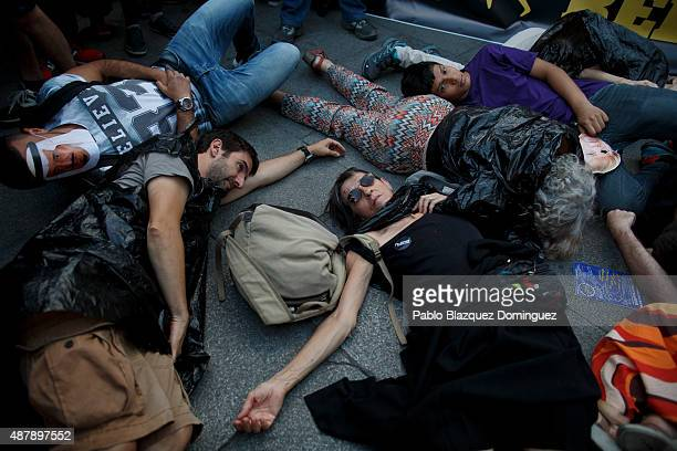 Protesters lay on the ground during a performance at the end of a demonstration to show solidarity and support for refugees on September 12 2015 in...
