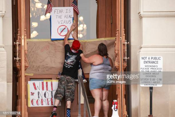 Protesters leave a signed placard for the Indiana Governor on the doors of the Indiana Statehouse during the We Will Not Comply anti mask rally....