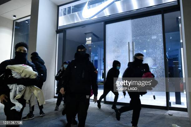 Protesters leave after breaking the window of a shop and holding clothes during clashes following a demonstration against the imprisonment of Spanish...