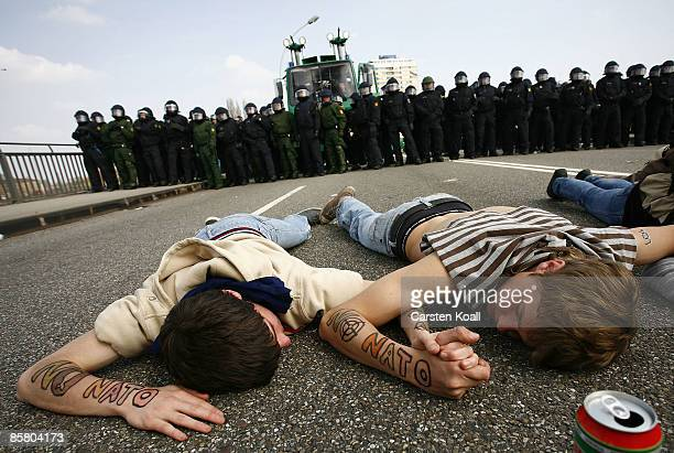Protesters lie on the ground of the Europa Bridge in front of the German riot police during clashes protesting against the ongoing NATO summit on...
