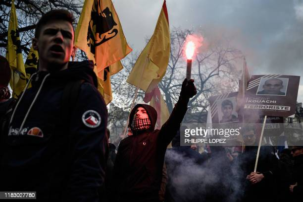Protesters light flares and hold flags as they take part in a demonstration against islamism organised by the far right group Generation Identitaire...