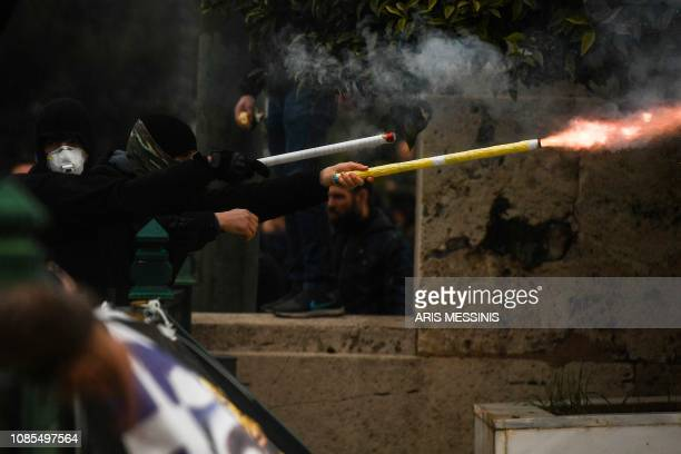 Protesters light flares during clashes with riot police during a demonstration against the agreement with Skopje to rename neighbouring country...