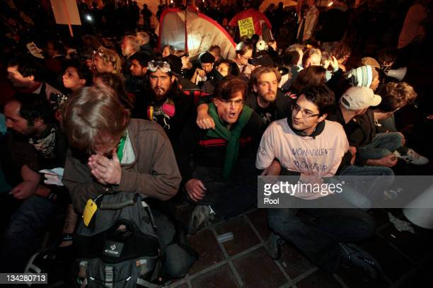 Protesters link arms and sit on the floor as they wait for members of the Los Angeles Police Department to move in and evict them from the Occupy LA...
