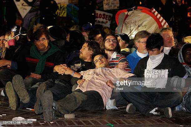Protesters link arms and wait to be arrested as Los Angeles Police Department officers enforce the eviction of the Occupy LA tent encampment outside...