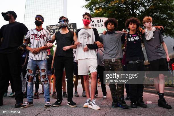 Protesters link arms during a demonstration on May 31 2020 in Atlanta Georgia Across the country protests have erupted following the recent death of...